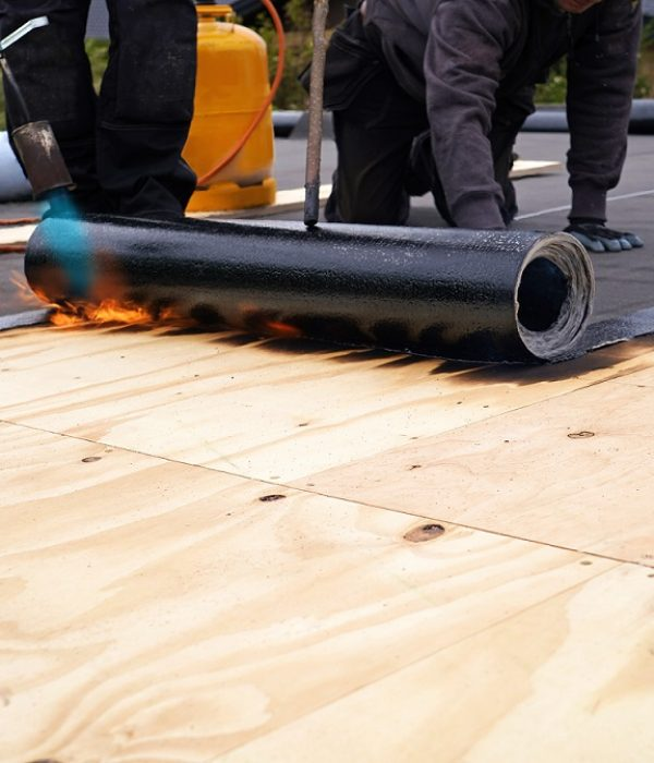 Two roofers are installing flat roof (bitumen) on residential property in Vaughan