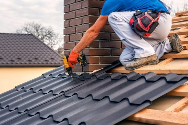 Metal roof installation with tin roof shingles with electric screwdriver near the chimney